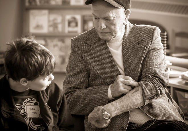 Karl Perl, a Holocaust survivor, shows the number the Nazis tattooed on his arm to a teenager during the Yom Hashoah Holocaust Remembrance Day service at the Harry & Rose Samson Family Jewish Community Center in April 2014.