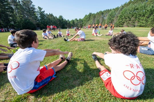 Boys stretch before a competition during the Red Arrow Olympics in 2019. The competition is an annual tradition at the summer camp in Woodruff.