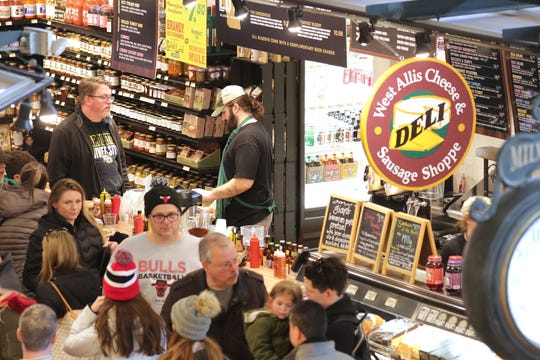 James Roufus, upper right, a cheesemonger at West Allis Cheese & Sausage Shoppe's location in the Third Ward, tends to a customer amid the crowd in the Milwaukee Public Market.