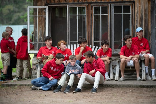 Boys sit outside a log cabin at Red Arrow Camp in Vilas County. The camp is celebrating its 100th anniversary in 2020.
