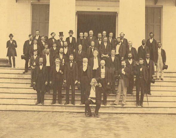 The Alabama State Senate in 1872. Jeremiah Haralson is at the right end of the third row from the bottom, holding a top hat.