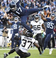 Tennessee Titans quarterback Ryan Tannehill (17) goes up high to score on a 21-yard touchdown run during the second quarter at Nissan Stadium Sunday, Nov. 24, 2019 in Nashville, Tenn.