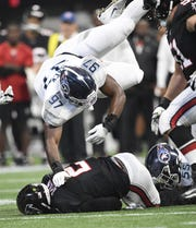 Tennessee Titans inside linebacker Jayon Brown (55) stops Atlanta Falcons quarterback Matt Ryan (2) as defensive tackle Isaiah Mack (97) goes up on a fourth down during the fourth  quarter at Mercedes-Benz Stadium Sunday, Sept. 29, 2019 in Atlanta, Ga.