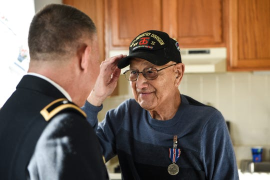 Robert Carlo, an Army veteran of World War II, salutes Mark Piterski, the state's deputy commissioner for veterans affairs, after receiving the Distinguished Service Medal at his apartment in Wayne on Jan. 22.