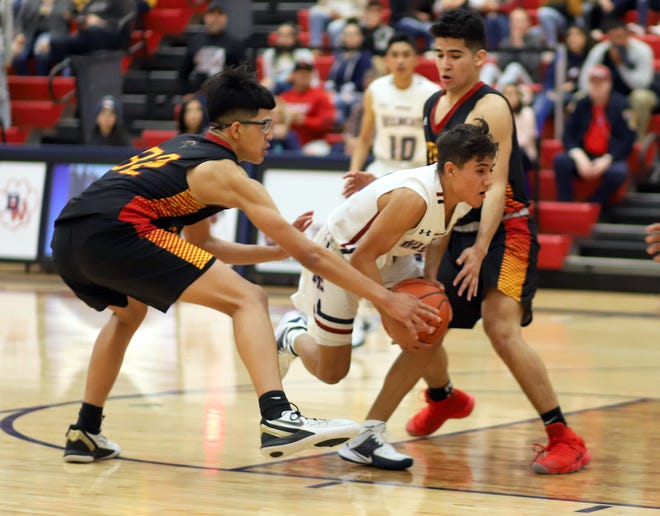 Senior Wildcat guard Ramiro Saenz (with ball) split two Centennial defenders on this play and scooped in an underhand shot to tie the game with 7.8 seconds left to play.