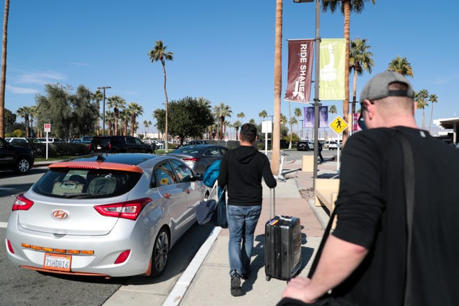 Passengers wait to be picked up by ride share services at Palm Springs International Airport on Wednesday, Jan. 22, 2020 in Palm Springs, Calif.