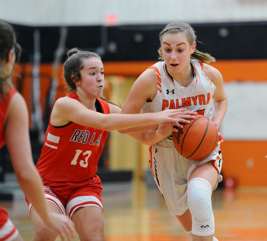 Palmyra's Zoe Smith Tries to drive the lane as Red Land's Zayda Crumpton (13) is on her.