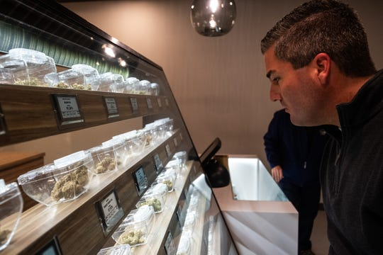 Port Huron City Manager James Freed looks over different kinds of medical marijuana arranged in a display case Tuesday, Jan. 21, 2020, at LIV Ferndale. The special containers used by the dispensary are designed to allow patients to inspect the product without physically touching it.