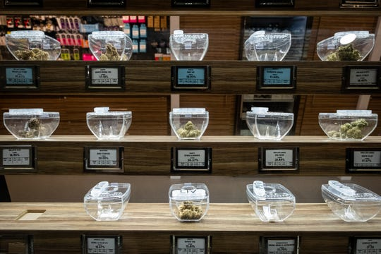 Different types of medical marijuana are arranged in containers on a shelf at LIV Ferndale.