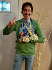 Highland resident William Hiemcke poses with his running medals.