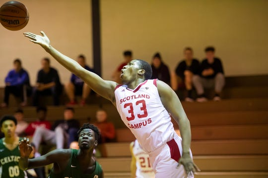 """Scotland Campus' Abou Ousmane extends to score on a layup during a game against The Patrick School in Scotland on Wednesday, Jan. 15, 2020. Ousmane, a senior 6'9"""" power forward from Brooklyn, NY, poured in 32 points along with 19 rebounds to help Scotland win, 92-74."""