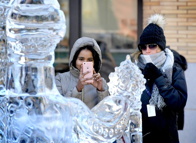 Sushmitha Chintapalli of Springettsbury Township, left, and Melissa Miller of Dover Township stop to look at one of the FestiveICE sculptures at Continental Square Wednesday, January 22, 2020. The coworkers were taking a walk during their lunchbreak. The early-week freezing temperatures that kept the downtown sculptures intact will give way to warmer weather through the weekend. Bill Kalina photo