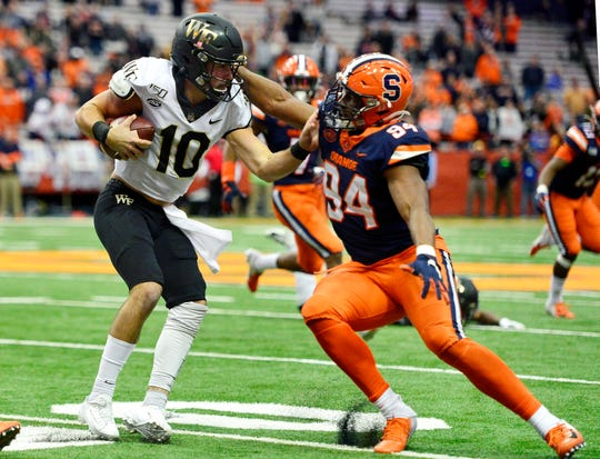 Wake Forest quarterback Sam Hartman is sacked by Syracuse defensive lineman Alton Robinson.