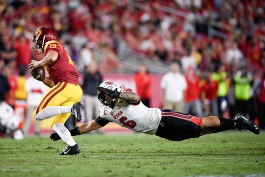 Utah's Bradlee Anae attempts to tackle USC quarterback Matt Fink.
