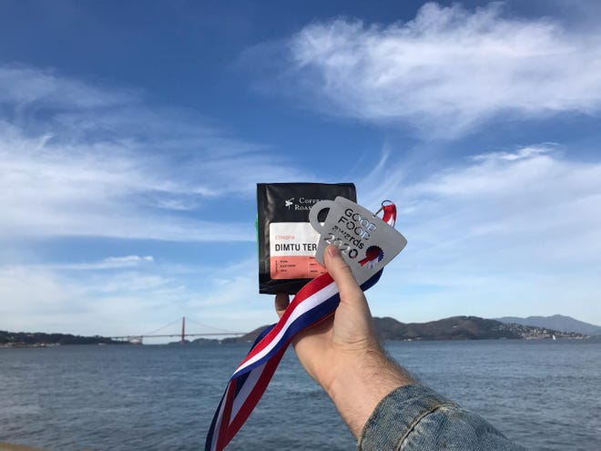 Andrew Fritz holds a bag of Coffea coffee and the Good Food award Coffea Roasterie received in San Francisco.