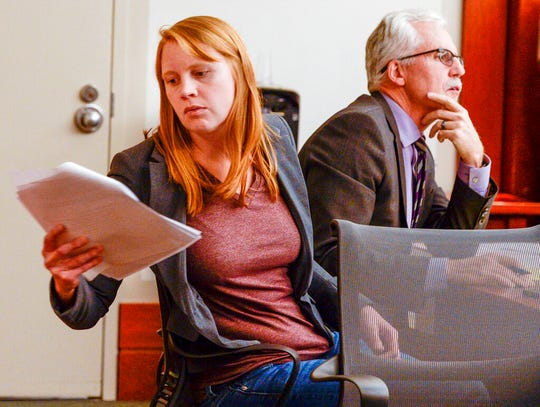 FILE - In this Nov. 19, 2019, file photo, Tilli Buchanan, left, reads a document in court as she sits with Randy Richards, right, her attorney, during deliberations in a case where Buchanan was charged with criminal lewdness involving a child, in Salt Lake City. Judge Kara Pettit refused on Tuesday, Jan. 21, 2020, to overturn part of Utah's lewdness law in a blow to Buchanan who's fighting criminal charges after her stepchildren saw her topless in her own home. Pettit sided with prosecutors who argued that lewdness is commonly understood to include women's breasts in American society, the Salt Lake Tribune reported. (Leah Hogsten/The Salt Lake Tribune via AP, File)