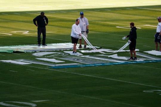 People prepare to paint the field during a tour of the Hard Rock Stadium on Tuesday, Jan. 21, 2020, ahead of Super Bowl LIV in Miami Gardens, Fla.