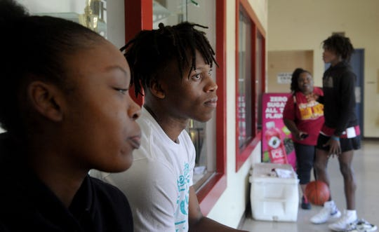 Mika Jarrett, left, and Stacy Johnson, along with Kai Johnson and the siblings' mother, Kika Johnson (in background), wait for Oxnard's team practices last Tuesday.