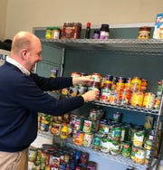 Sabater Elementary School Social Worker Ken Smith arranges inventory at the school's food pantry that is prepared to serve 100 families at the school and another 100 families from neighboring Dallago Preschool.