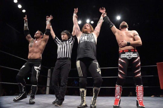 Ben Manthe, third from left in tank top, raises his hands in victory with fellow wrestlers Vic Capri (left) and Justin Dredd (right) and a referee from Tokyo, Japan. Manthe wrestles as Bulletproof Ben McCoy.
