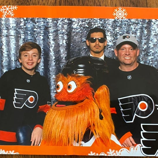 Chris Greenwell, right, poses with Gritty, his son and Gritty's handler at a November event.