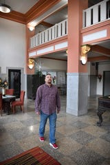 Matthew Smith walks through the lobby of The Holt, built in 1910 as the Holt Hotel. The building was closed and derelict for many years before Smith and other volunteers cleaned it out.