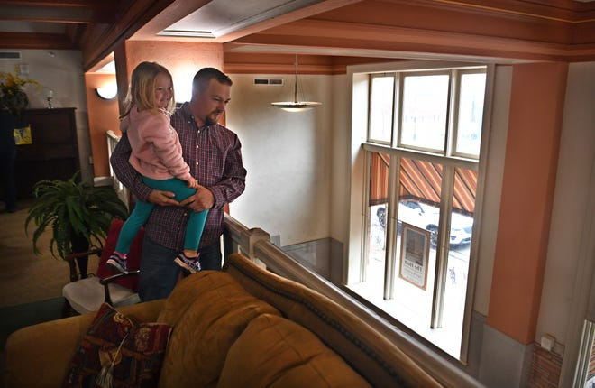 Matthew Smith and his daughter, Juliana, 5, look down from the second floor mezzanine of The Holt into the lobby. As a Boy Scout in 2001, Smith made an Eagle Scout project out of cleaning out the abandoned Holt Hotel to encourage renovation.