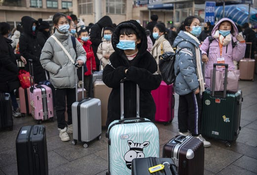 Chinese children wear protective masks as they wait to board trains at Beijing Railway station before the annual Spring Festival on Jan. 21, 2020 in Beijing, China. The number of cases of a deadly new coronavirus rose to nearly 300 in mainland China Tuesday as health officials stepped up efforts to contain the spread of the pneumonia-like disease which medicals experts confirmed can be passed from human to human. The number of those who have died from the virus in China climbed to six on Tuesday and cases have been reported in other parts of Asia including in Thailand, Japan, Taiwan and South Korea.