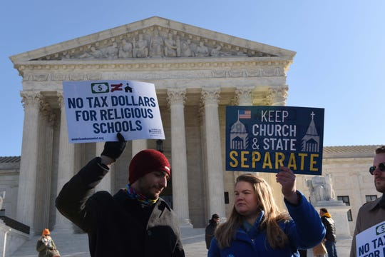 Supporters of public schools demonstrate outside the Supreme Court on Jan. 22 as justices consider a challenge to state bans on funding religious schools.