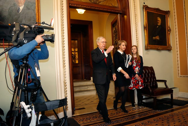 Senate Majority Leader Mitch McConnell, R-Ky., center, leaves the Senate chamber during the a break in the impeachment trial of President Donald Trump on charges of abuse of power and obstruction of Congress, at the Capitol in Washington, Tuesday, Jan. 21, 2020. (AP Photo/Julio Cortez)