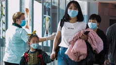 A health officer screens arriving passengers from China at Changi International Airport in Singapore on January 22, 2020 as authorities increased measure against coronavirus.