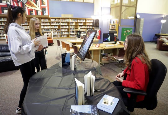 "Neenah High School student Natalie Frank, who wrote a novel, talks with fellow students during a book signing event Wednesday at Neenah High School.  Titled ""When Sea Becomes Cemetery,"" the historical fiction novel is about U-505, a German World War II submarine that was captured by U.S. sailors."