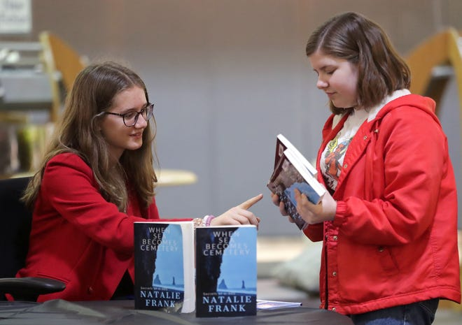 Neenah High School student and author Natalie Frank chats with fellow student Olivia Cannon during a book signing event Wednesday at Neenah High School. Frank worked on the book for several months during her freshman year of high school, and it was released in May.