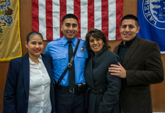 Police officer Willie Cuzco poses for a photo with his family after being sworn in as a member of the Lakewood Police Department. Police chief Greg Meyer said that the academy's graduating class reflects the township's population and hopes this helps bridge gaps with the community.