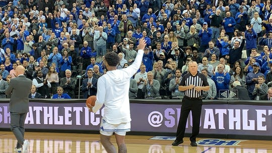 Myles Powell waves to Seton Hall fans after receiving a ball commemorating his 2,000th collegiate point.