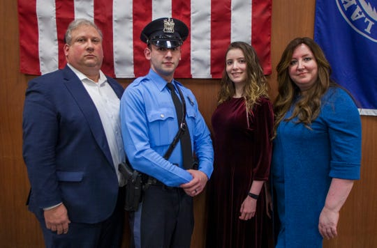 Police officer Michael Wolf, in uniform, poses with his family after being sworn in as the first Orthodox policeman to join the Lakewood Police Department. With his arrival, township police expect to have closer communication with the local Orthodox Jewish community.