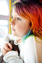"""Emma Smith, 8, looks out a window of her home in Arden January 17, 2020. """"She's still dealing with issues with teachers and trust,"""" said Emma's mother, Amy, of her transgender daughter."""