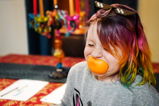 Emma laughs with an orange in her mouth and she hangs out with her brother in their kitchen in Arden January 17, 2020.