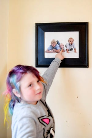 Emma Smith, 8, points to a photo of herself as a baby, when her name was Colton.
