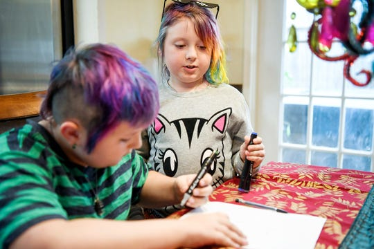 Emma talks to her brother, Miller, as he draws with markers in their home in Arden January 17, 2020.
