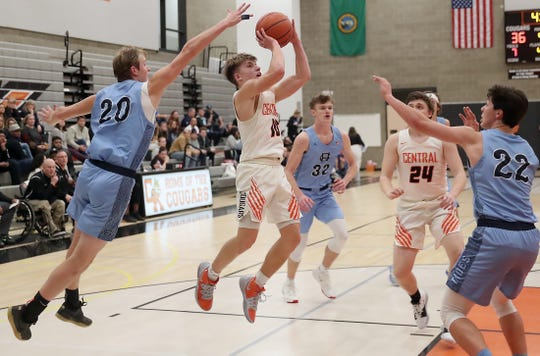 Gig Harbor's Jack Emery (20) tries to block the shot of Central Kitsap's Colby White (10) during the second half of their game in Silverdale on Wednesday, Jan. 22, 2020.