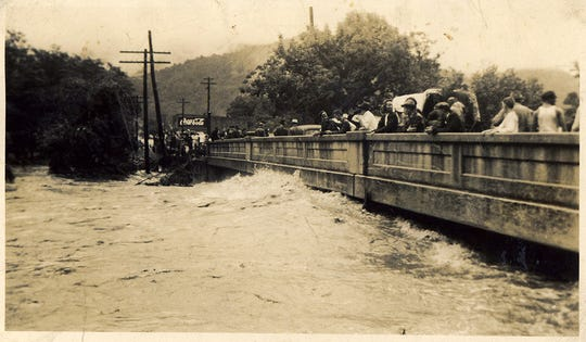 """In this photograph from the Swannanoa Valley Museum and History Center's collections, valley residents watch the engorged waters of the Swannanoa River from the Whitson Avenue bridge in Swannanoa during the Great Flood of 1940. The flood was caused by a combination of heavy rain in the early weeks of August 1940 followed by a hurricane that brought additional rainfall for five days. The result was that over 21 inches of rain battered parts of Western North Carolina. According to the Tennessee Valley Authority's publication Floods on French Broad and Swannanoa Rivers (1960), """"In the Swannanoa basin [rainfall] amounts ranged from five inches at Asheville to 15 inches on [the] North Fork watershed and 16 inches on upper Bull Creek."""" The flood caused damage to roadways, bridges, homes, and other infrastructure throughout the valley."""