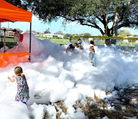 Children play in foam pumped out by a machine First United Methodist Church of Melbourne brought to Carver Park for a picnic celebrating the completion of Habitat for Humanity's Cedarwood community in Melbourne.