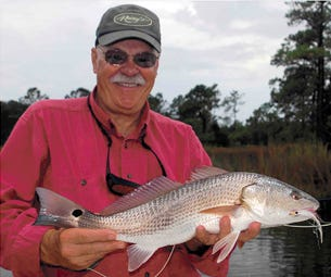 Bob Clouser, shown with a redfish that he caught on his famous Clouser Minnow fly.