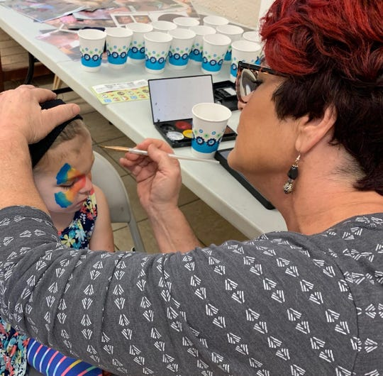 Sandra Peters of Mosaic Church in Palm Bay paints a butterfly on Mia Hutker's face during a Habitat for Humanity of Brevard picnic in Melbourne.
