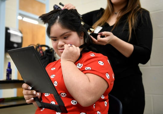 India Garza looks at herself in the mirror while an Avid employee curls her hair before the Special Hearts Prom, Thursday, Jan. 23, 2020, at Moody High School. The program is designed for students with special needs who would not otherwise be able to attend a traditional prom.