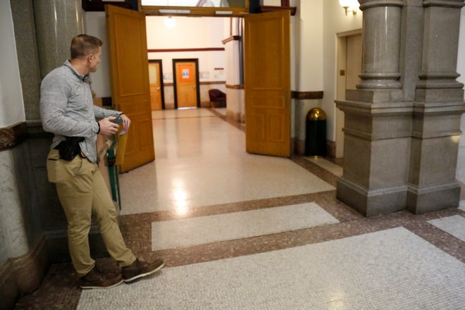 A process server from the Ohio Auditor of State waits outside of the city council chambers before a meeting at Cincinnati City Hall in downtown Cincinnati on Thursday, Jan. 23, 2020. The server left the building shortly after it was announced that council member Tamaya Dennard would not be attending.