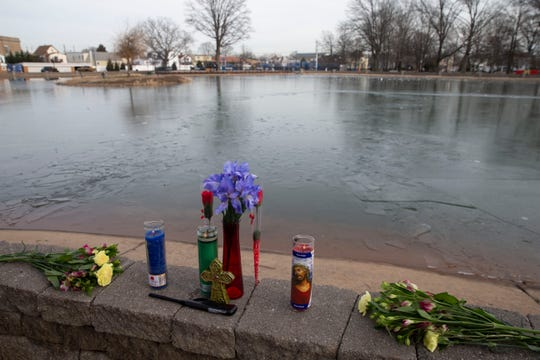 Candles and flowers are shown on a wall near broken on the surface of the pond in Carteret Park Thursday afternoon, January 23, 2020.   A young man who fell through an icy pond here was transported to University Hospital in Newark Wednesday night and later died there.