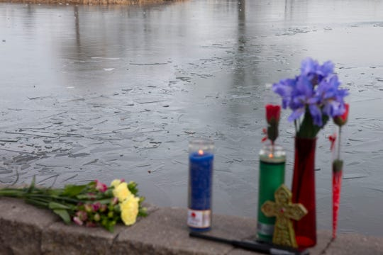 Candles and flowers line a wall near broken ice on the surface of the pond in Carteret Park Thursday afternoon, January 23, 2020.   A young man who fell through an icy pond here was being transported to University Hospital in Newark Wednesday night and later died there.