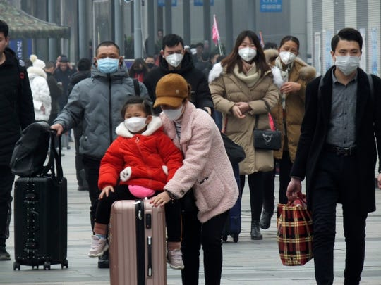 Travelers wear face masks as they walk outside a train station in Yichang in southern China's Hubei province, Tuesday, Jan. 21, 2020. Face masks sold out and temperature checks at airports and train stations became the new norm as China strove Tuesday to control the outbreak of a new virus that has reached four other countries and territories and threatens to spread further during the Lunar New Year travel rush. (Chinatopix via AP)